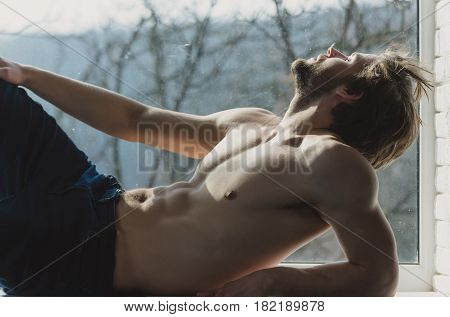 Handsome man or muscular sexy macho with fit naked torso six packs abs biceps triceps lying on window sill on blurred natural background. Face with closed eyes relaxing and day dreaming poster