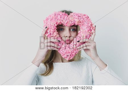 Pretty girl or cute woman with blond hair and adorable happy face in white sweater blouse or sweatshirt with pink wicker heart for valentines day on grey background