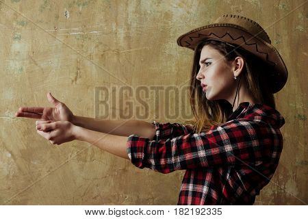 Pretty girl or beautiful woman with blond long hair in stylish cowboy hat and red plaid shirt showing finger gun hand gesture on beige wall background. Nonverbal communication gunfighter