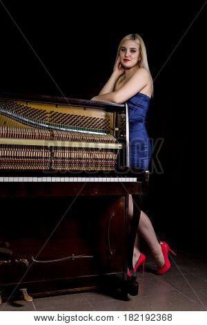 fashion young woman stands next to old retro wooden piano with keyboard and posing.