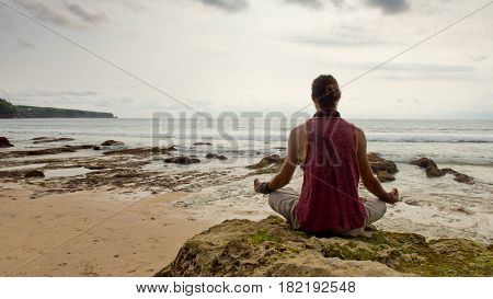 A young man meditates in a lotus pose on the beach sitting on a rock. Sunset. Dreamland beach. Bali Indonesia.