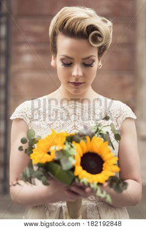 Beautiful young bride posing in a wedding dress in a retro cobble street holding a sunflower bouquet