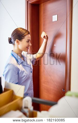 Young concierge knocking on the door of hotel room