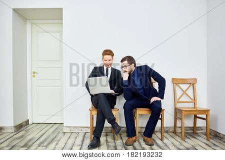Portrait of two business people using laptop sitting on chairs in waiting room outside office