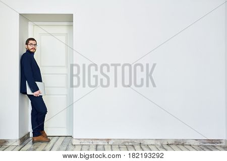 Bearded man in glasses leaning on doorway holding laptop computer and looking at camera next to blank white wall in office