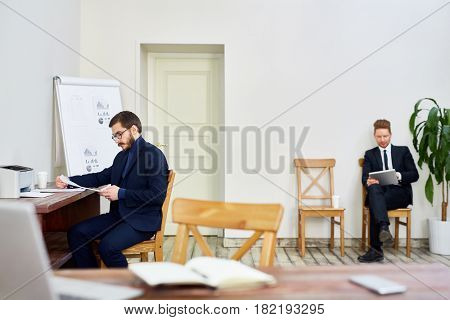 Two business people working in old-school business office, one man reading documentation at desk, other man using tablet  sitting on chair