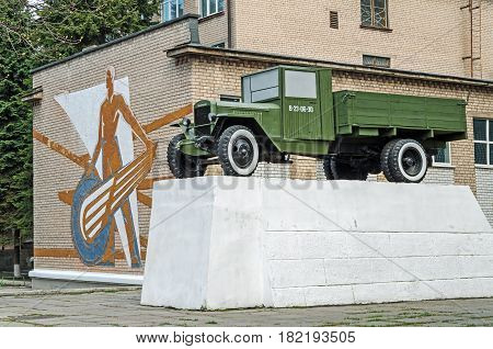 Dnipro Ukraine - April 05 2017: Classic Soviet monument to a UralZIS truck against a wall with a mural from the times of USSR