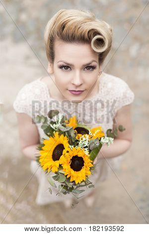 Top view of a beautiful young bride in a wedding dress standing on a cobble road and holding a sunflower bouquet