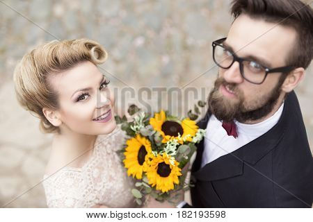 Top view of a newlywed couple standing and posing for a photo shooting
