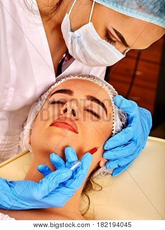 Filler injection for female face. Plastic aesthetic facial surgery and in clinic. Beauty woman giving injections in cosmetology room. Doctor in medical mask and gloves with syringe injects cheeks drug
