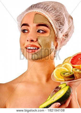 Avocado clay face mask. Woman in medical hat holding half of green fruit on plate isolated background. Facial beautiful treatment procedure concept.