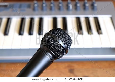 Black vocal microphone close up against defocus electronic synthesizer keyboard with many control knobs in silver plastic body as background