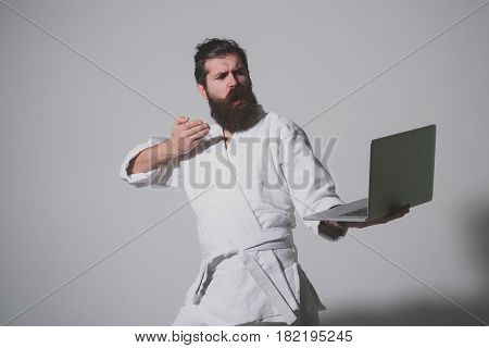 bearded karate man long beard brutal caucasian hipster with moustache in white kimono holds laptop with serious face on grey background unshaven guy