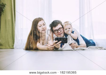 Family Mom, Dad And Baby Are Doing Selfie On Phone Lying On The Floor