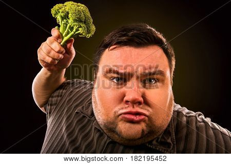 Diet fat man eating healthy food . Health breakfast with vegetables broccoli for overweight person. Male trying to lose weight but he can no longer eat cabbage.