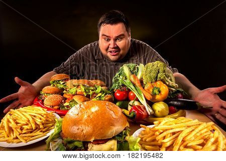 Diet fat man who makes choice between healthy and unhealthy food . Overweight male with hamburgers, french fries and vegetables trays trying to lose weight first time .