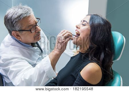 Dentist at workplace examining patient. Female in dental chair. Highly qualified stomatologist.