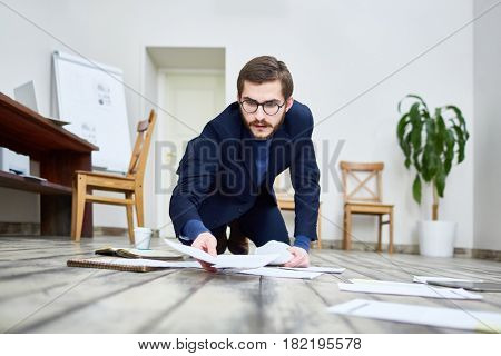 Portrait of middle aged bearded man wearing glasses laying out documents on floor in office