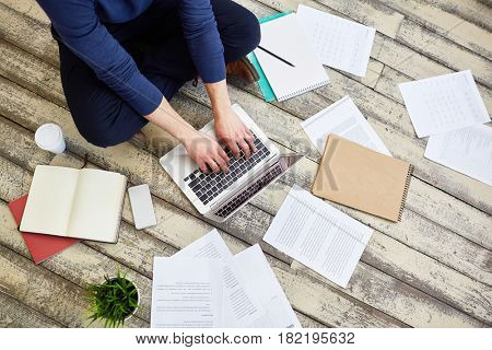 Top view of unrecognizable freelancer working sitting cross legged on wooden floor, using laptop computer with documents and business supplies laid out around