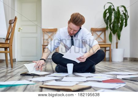 Portrait of busy man speaking by phone and sorting documents sitting on floor in office