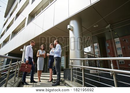 Group of young business colleagues smiling and chatting outside modern office building, leaving work