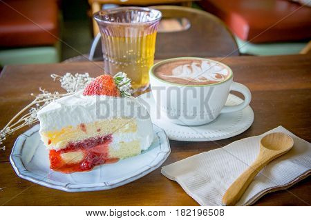 coffee cup and delicious cake strawberry and relax time mobile on table in coffee shop