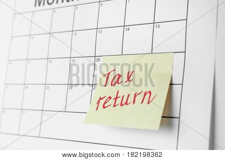 Note with text and calendar. Tax return concept