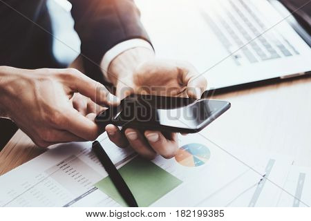 Closeup view of male hands holding modern mobile phone with and pointing finger to home button.Horizontal, blurred background, visual effects