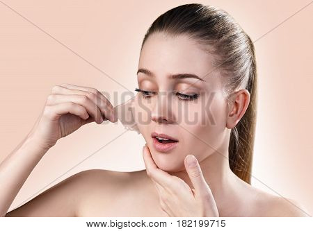 Beautiful woman remove her old dry skin from face. Over beige background.