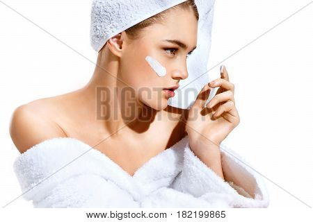 Young woman with flawless skin applying moisturizing cream on her face. Photo of woman after bath in white bathrobe and towel on white background. Skin care concept