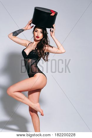 Sexy Woman With Red Lips In Black Bodysuit With Box