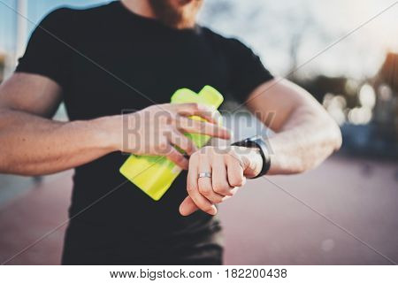 Muscular young athlete checking heart rate and burned calories on his smartphone application after good workout outdoor session on sunny park.Blurred background