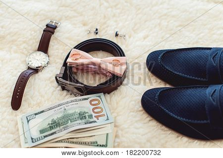 Close up of modern man accessories. Biege bowtie, leather shoes, belt, watch, cufflinks, money and wedding rings. formal style of wearing