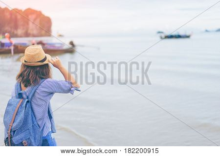 Young woman traveler with sky blue backpack and hat looking the sea with long boat thailand background from Ao Nang Beach Krabi. Traveling in Krabi Thailand Traveler summer concept