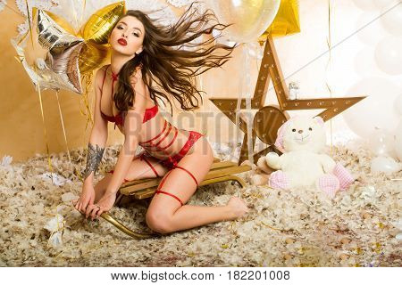 pajamas party celebration pretty woman or cute sexy girl in erotic lingerie of bra panties has red lips sitting on sledge at teddy bear toy festive golden balloons white snowflakes feathers