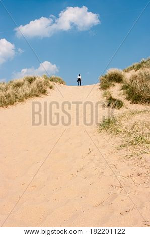 Young woman standing at the top of a steep sand dune in Burnham Overy Staithe Norfolk UK.