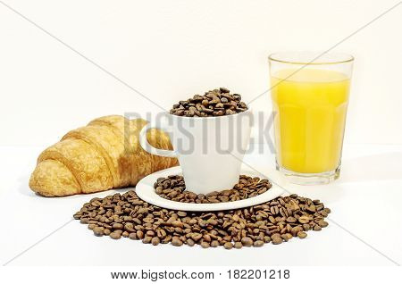 Cup of coffee filed with coffee beans with croissants and orange juice on white background