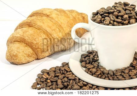 Cup of coffee filed with coffee beans with croissants on white background, close