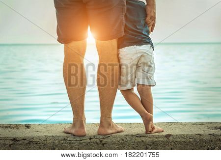 Father and son stay on the sea beach under sunlight at summer time. Close-up foots view on the sealine background at sunny day.