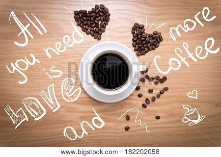 Hot cup of espresso and heart shape made from coffee beans on wooden surface. White mug of hot drink. Sign: All you need is love and more coffee.