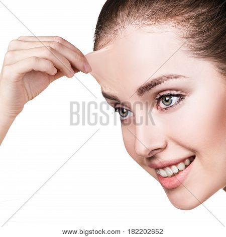 Beautiful woman remove her old dry skin from forehead. Over gray background.