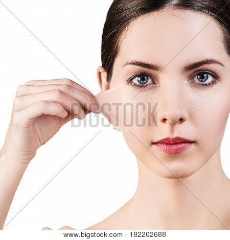 Beautiful woman remove her old dry skin from face. Over gray background.