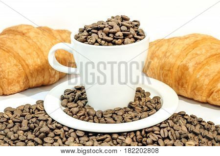 Cup of coffee filled with coffee beans with croissants, cinnamon and orange juice on white background