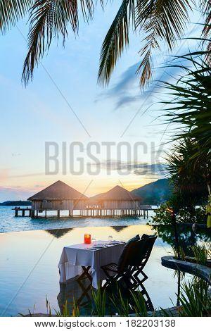 Romantic luxury dinner setting at tropical resort on sunset