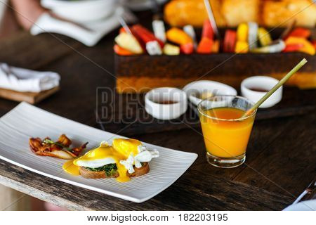 Poached eggs served for breakfast with bacon and juice