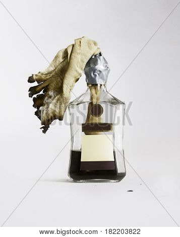 Incendiary mixture in a bottle of cognac on a white background.