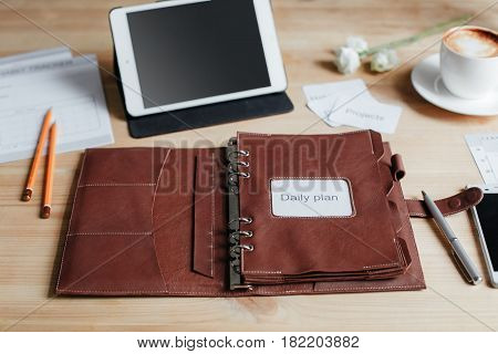 Notepad For Planning, Two Pencils, A Pen, A Smartphone, And A Touch Pad On A Wooden Table.