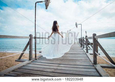 Fashion bride walking down pier on the beach in a white dress. Beautiful girl walks barefoot down the beach. Honeymoon.