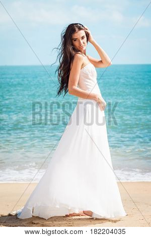 Bride walking down the sea coast in a white dress. Beautiful girl walks barefoot down the beach. Wedding day. Romantic atmosphere in tropical country. Caucasian model with long brown hair.