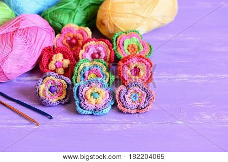Crochet colorful flowers set. Crochet flower ornaments, cotton yarn, hooks on a wooden background with copy space for text. Amusing hobby idea for women and kids. Closeup